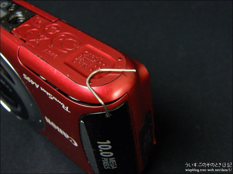 クリップで固定したコンパクトデジタルカメラの電池ホルダー